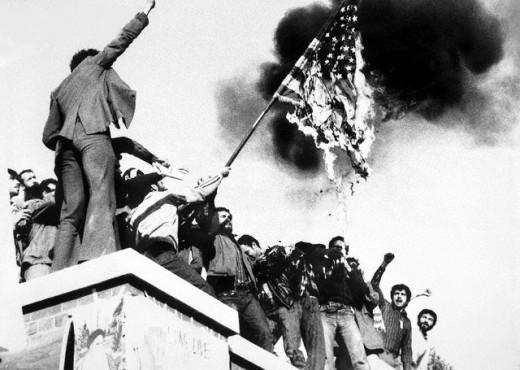 Iranian revolutionaries burning the American flag atop the American Embassy in Tehran 1979.