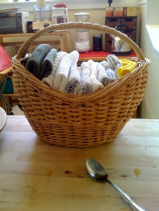 Reusable dishcloths in basket where the paper-towels used to stand on their vertical roller