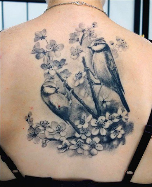 A beautiful tattoo of birds and cherry blossoms.