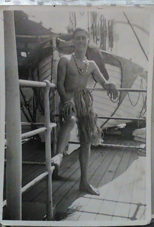 Gun crew rating with grass skirt(!), Pacific, 1945