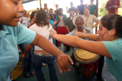 Whole families dance, sing, and celebrate to the beat of the drums and music.