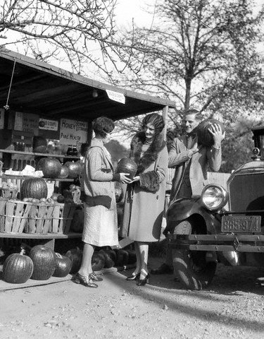 couple in the 1920s shop for fresh produce at a local produce stand