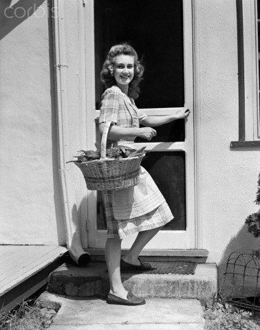 woman in the 1950s returns from a produce stand after a successful day of shopping for tasty produce for her family