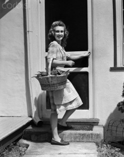 woman in the 1950's returns from a produce stand after a successful day of shopping for tasty produce for her family