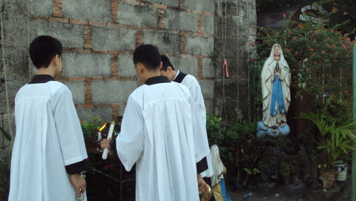Children of Calumpit town in the Philippines light candles for Virgin Mary's statue