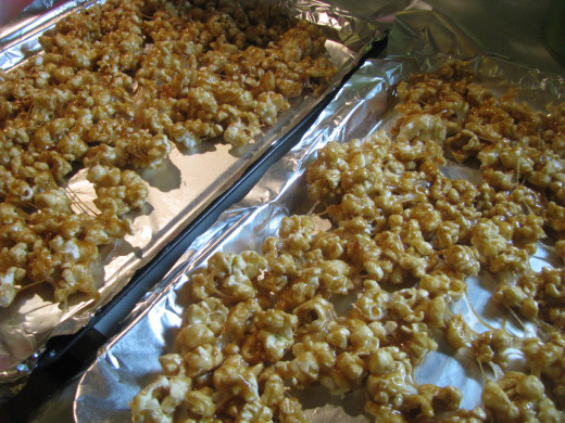 Spread caramel corn on two sheet trays that are lined with foil and sprayed with oil spray.  Bake.