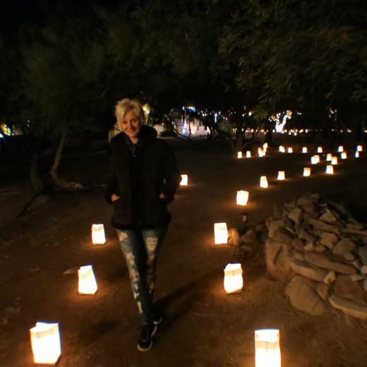 My wife on path illuminated with traditional Luminaria consisting of small paper bags with a candle inside
