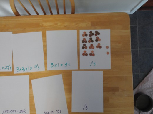 All the the 3's place value tokens are turned in to 1's and added to the two already there.