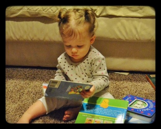 Books with realistic photos encourage a child's interest in reading at an early age. (Courtesy of L. Harvey, 2014)