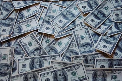Piles of money, one hundred dollar bills.