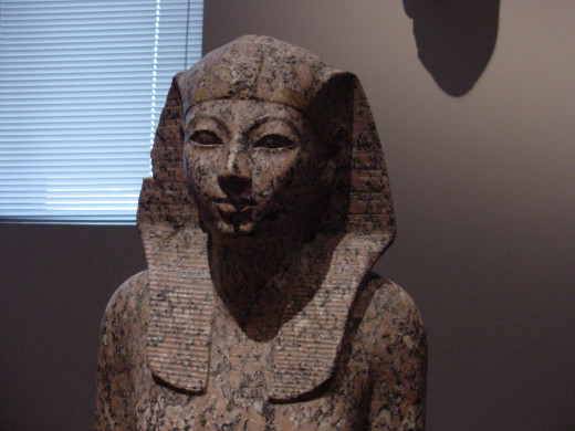 A statue of  Hatshepsut. A beautiful red granite statue that almost has a smile on its face.