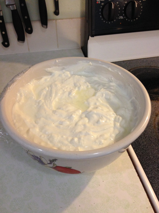 Big bowl of Greek yogurt ready to eat.  You can see a little clear yellow whey separated on top of the yogurt