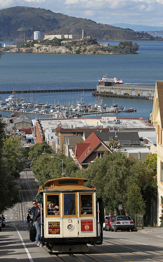 One of San Francisco's cable cars along with a view of Alcatraz in the bay