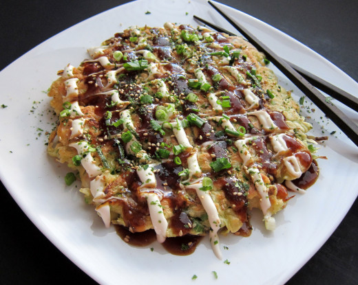 "Often called ""Japanese Pancake/Pizza"", okonomiyaki is a savory dish more like an omelette and is famous for the regional variations in Osaka and Hiroshima."