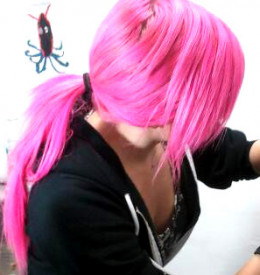 Female piercer with pink hair in a ponytail. (This is the cropped version of the photo. The larger, uncropped/unedited version can be found by clicking on the link.)