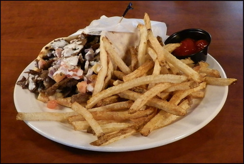 The Gyro Sandwich Stuffed with Mediterranean Salad and Tzatziki Sauce!   To View More Tasty Dishes Take A Look At Their Impressive Glossary/ Menu To Find Out  More About Your Favorite Mediterranean Dishes!