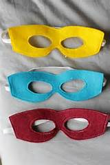 HERO MASKS Create a stencil shape of a mask on a stiff surface and trace this onto the backside of a piece of cloth from any kind of clothing. Cut out. Make holes for long strings to tie on each side.