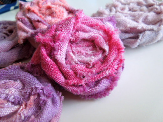 Roses with Fabric Strips. Buy cloth dye at a craft store. In glass bowls, dye white fabric various tones of red, pink, and purple. Lay out to dry. Scrunch and fold strips to resemble flowers. Sew back using heavy needle and thick thread.