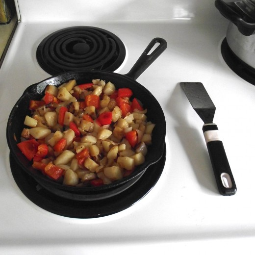 Potatoes and red peppers being cooked up in a cast iron frying pan.