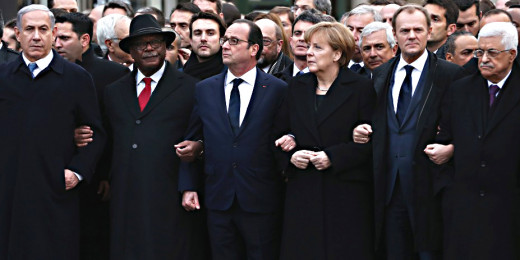World leaders led by François Hollande of France walk with linked arms. Most notably, on the left is the Israeli prime minister. On the right is the Palestinian president