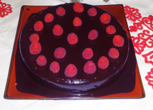 Walnut-cake with chocolate glaze and raspberry topping    The cake base uses ground walnuts instead of flour.