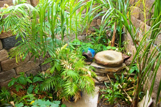 Palm trunks originally held back the soils left to right horizontally in the photo under the metate stone,