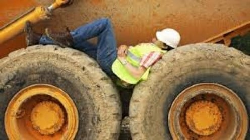 This worker looks as if he is sleeping, but in fact he is inspecting an area on this earth-mover