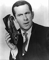 Don Adams, playing Maxwell Smart, aka Agent 86, in the 1960s TV series, Get .Smart. He never goes anywhere without his iconic shoe phone.  The Cone of Silence is another gadget used in the show. Unfortunately, it never worked.