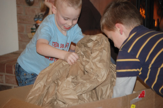 Kids digging into a present in a big box