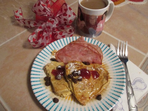 Heart shaped French Toast with strawberry jam, chocolate chips, maple syrup and ham. The pictures on the cup are some of my Valentines.  My husband and two of my granddaughters.