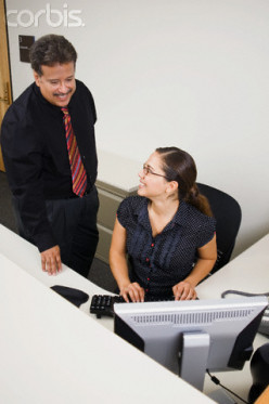 The clerk, girl at PC, listens to her assistant manager tell her about the new client