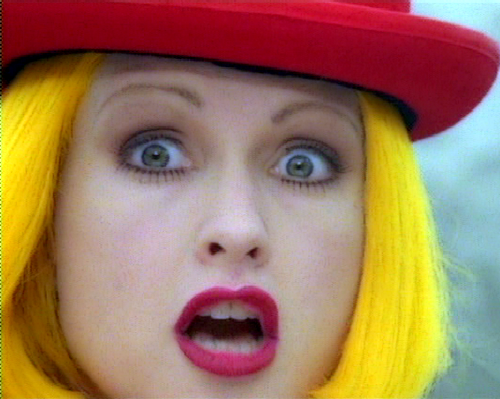 Cyndi Lauper with yellow hair and a red hat.