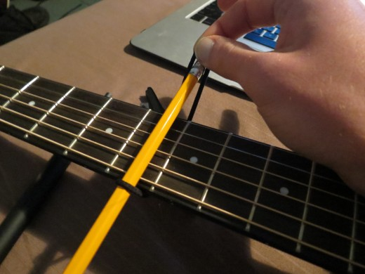 Now stretch the band behind the neck so it meets the bottom of the pencil.