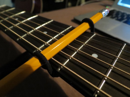 Now the makeshift capo is secure, but as I said before it will take a few more to achieve the right amount of tension. Simply repeat this until the strings play clean with no buzzing.