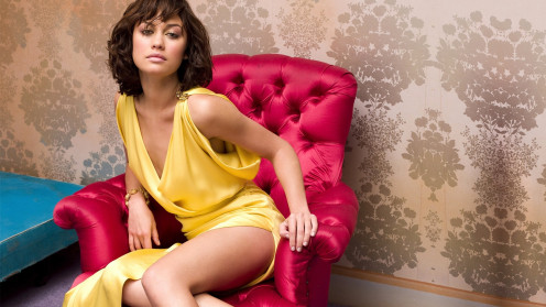 Olga Kurylenko in a yellow dress on  a love seat