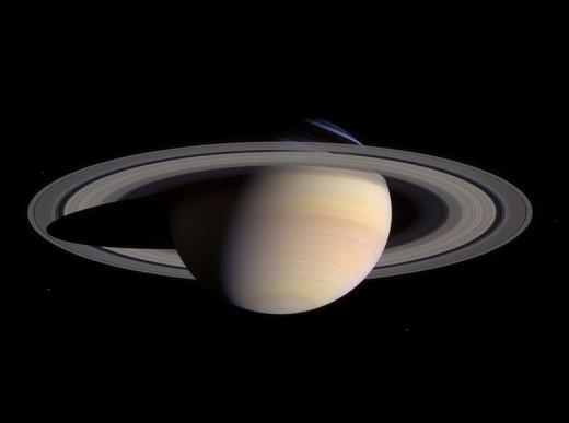 Saturn in natural color, photographed by Cassini in 2004. The planet's impressive and distinctive rings can clearly be seen.  Named after the Roman god of agriculture, this gas giant is over 95 times more huge than Earth.