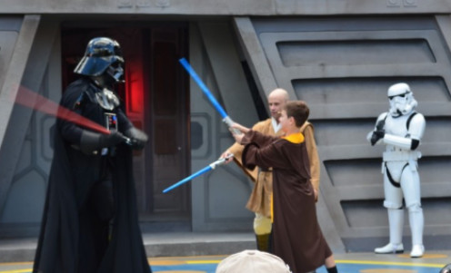Young visitors to Disney's Hollywood Studios test their light saber fighting skills against Darth Vader