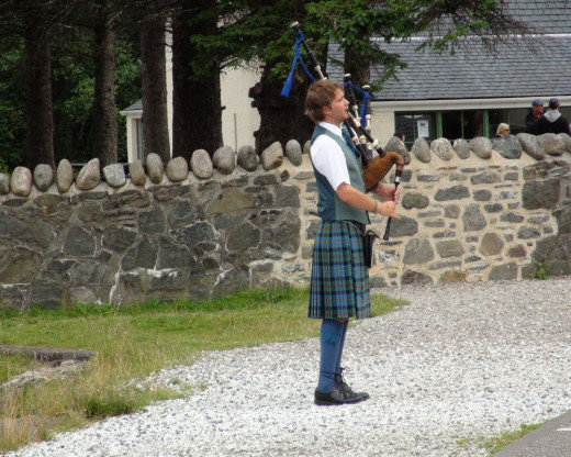 "A ""Celtie"" playing the Bagpipes outside of Eilean Donan Castle.  We had the benefit of listening to these musicians at several tourist attractions.  They are still very popular and very skilled.  The youngest musician we listened to was around 12."