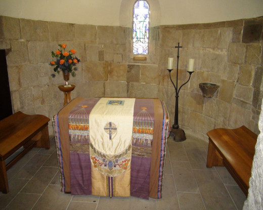 Photograph taken from  inside the small chapel at the castle.  This chapel is adorned by small, narrow stained glass windows and the necessary alter, candle, and paraments.  The seating space is very limited.
