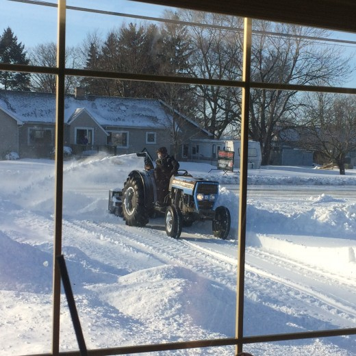 A photo of my dad snow blowing so that we could leave our driveway.