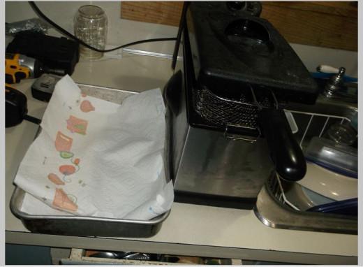 Turn fryer on. Place paper towel in metal cake pan.