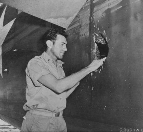 1st Lt Louis Zamperini, peers through a hole in his B-24D Liberator Superman made by a 20mm shell over Nauru, Apr 18 1943