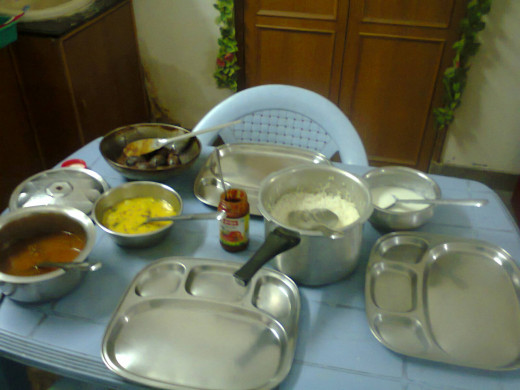 Meals ready for dinner. Rice in cooker, yellow dish 'dal', curry in deep pan, rasam on left and curd on right & pickle in bottle.