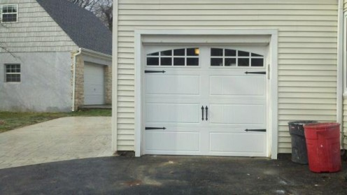 This is a white insulated garage door with arched glass and black iron hardware.