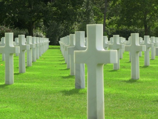 Kneeling to line up these crosses at the cemetery at Omaha Beach, Normandy, France.