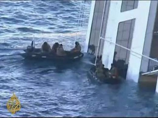 Filipino crew helping Costa Concordia passengers ride in life boats.