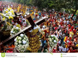 A young girl help people have their towel wipe the face of replica statue of the Black Nazarene.