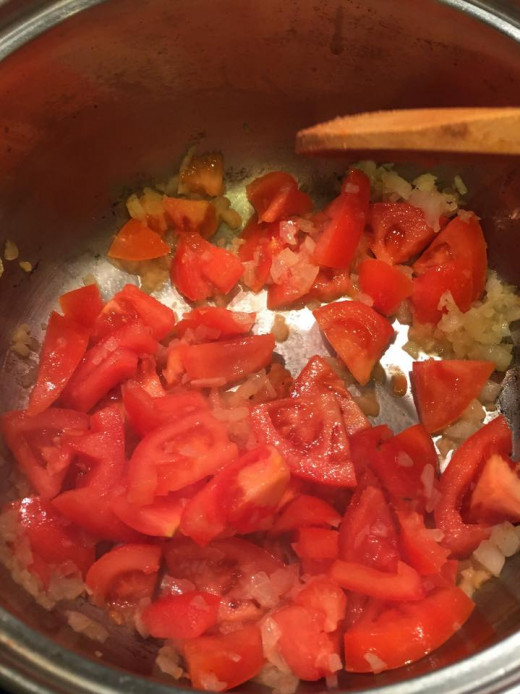 Then, adding the tomatoes in the pan until it is well cooked.