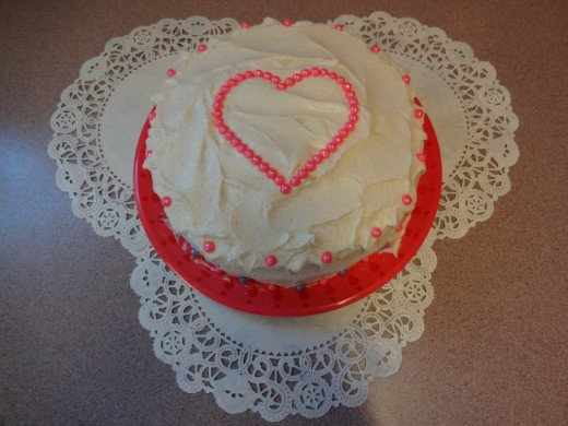 Candy pearls placed on the top in the shape of a heart to decorate this cake makes it special for Valentine's Day.