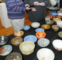 A table of bowls created by local artists for the Empty Bowl fundraiser. Attendees purchase a bowl and receive a lunch of soup in return. All proceeds go toward the Alton Crisis Food Center.